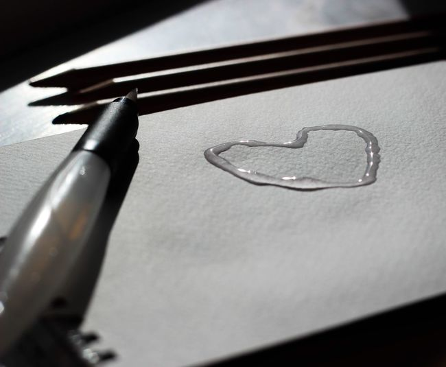 Close-up of heart shape made from glue on tissue paper by pencils