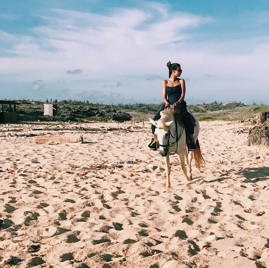Woman riding horse on sand against sky