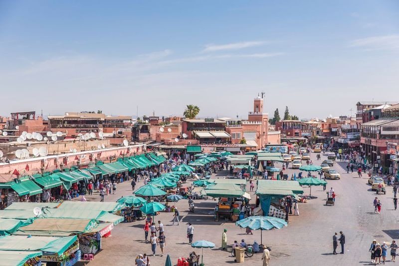 Large Group Of People Crowded High Angle View Market Stall Crowd Town Square Outdoors Real People Retail  Architecture Marrakech Street Photography Morroco Day Cloud - Sky Building Exterior Built Structure City Life Group Of People Sidewalk Cafe Market Travel Destinations