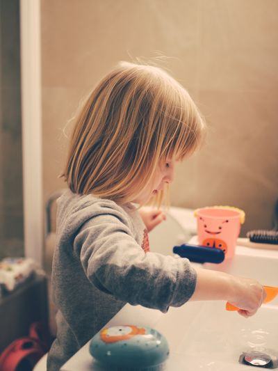 Side view of girl washing toys in sink at home