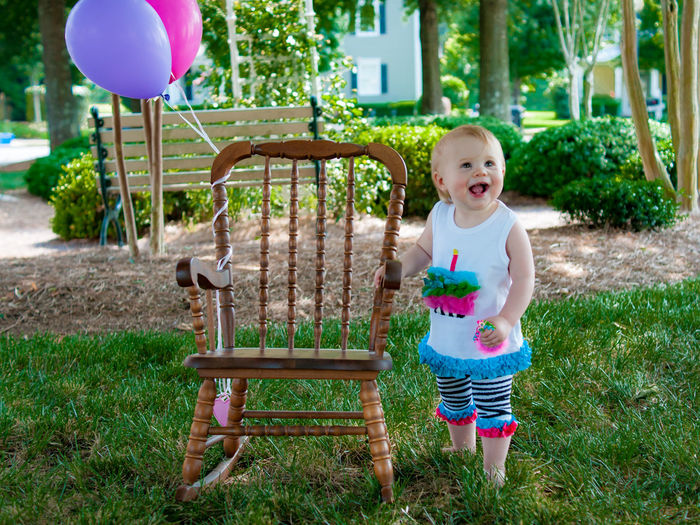Innocent girl standing by rocking chair with balloons at park