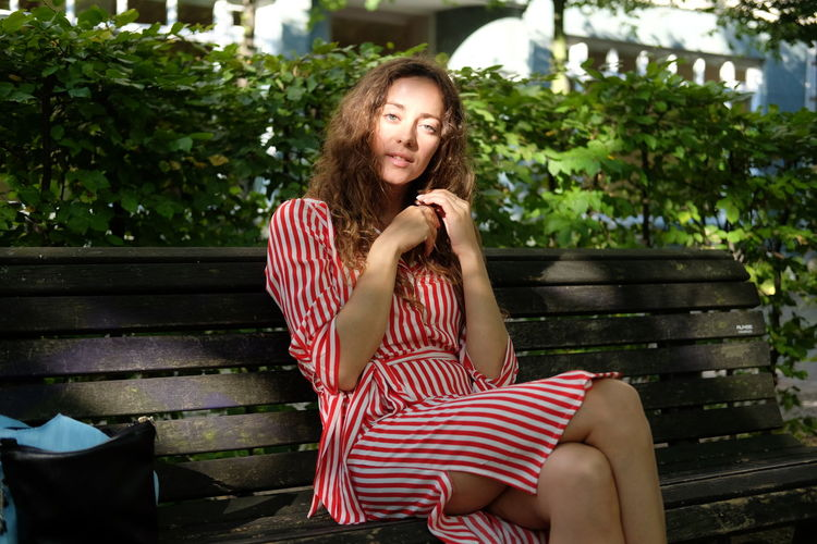 Woman with hand on chin looking away while sitting on bench