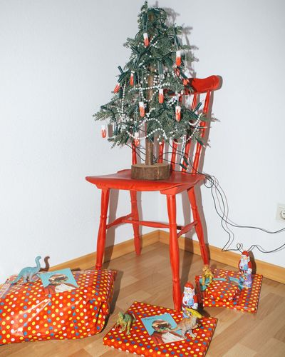 Christmas tree on table against wall at home