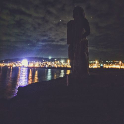 Statue by illuminated city against sky at night