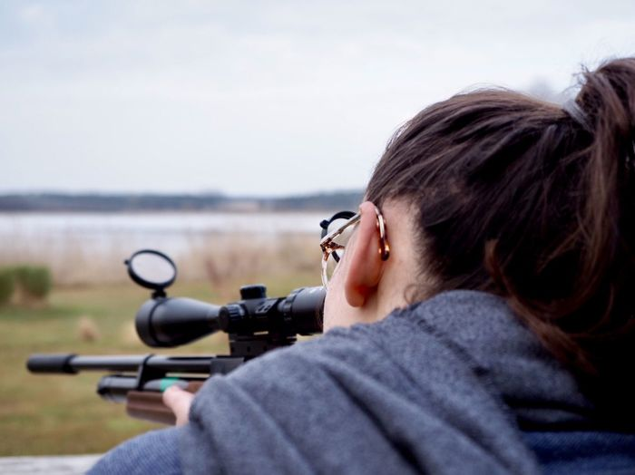 Close-Up Of Woman Aiming With Rifle Against Sky