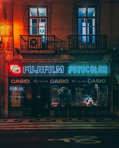 Neon Bikelane Casio Fuji Street Lisbon Shop Neon Text Building Exterior Architecture Communication Built Structure Window Illuminated Outdoors No People City Night