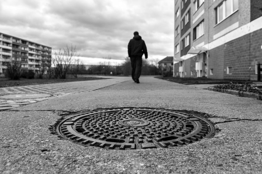 Same place, same angle, different time, different result. Compare this picture which has been taken earlier: https://www.eyeem.com/p/74428996 Black & White Black And White Bleak City City Life Cloudy Day Dreary Footpath Leading Leading Lines Pivotal Ideas Man Manhole  Manhole Cover Moody Moody Sky Overcast Pavement Perspective Street Street Photography Urban Walking Showcase: February