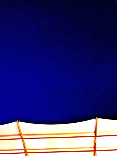 Low angle view of illuminated wall against blue sky