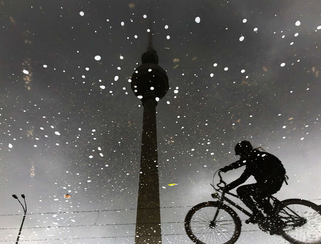 Fernsehturm Berlin  Reflection TV Tower Bicycle Cold Temperature Full Length Leisure Activity Lifestyles Light Men Nature One Person Outdoors Rain Real People Riding Silhouette Sky Snow Snowing Street Street Light Transportation