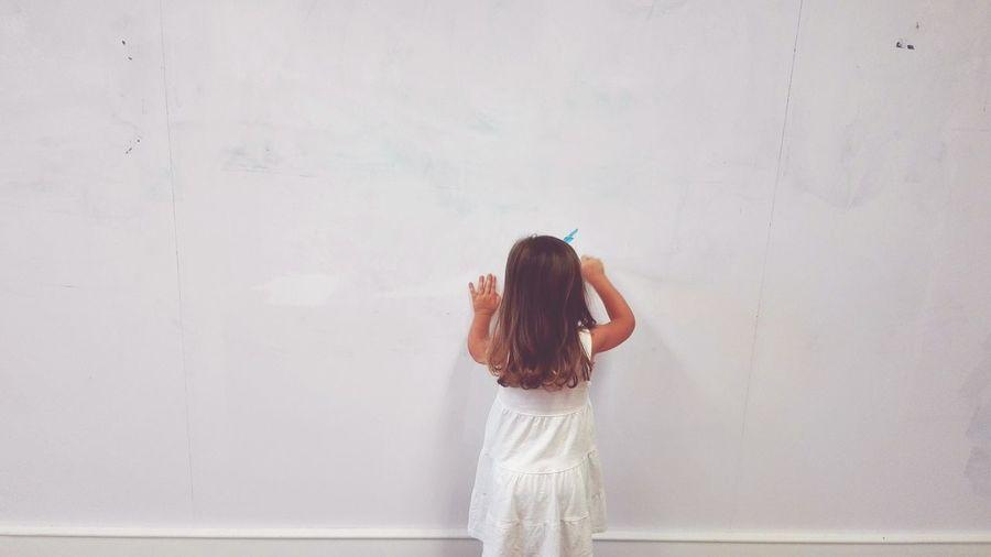 Girl Standing Against White Wall
