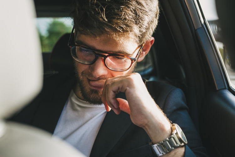 Close-up of businessman sitting in car