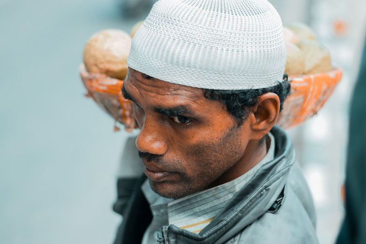 Close-up of market vendor looking away