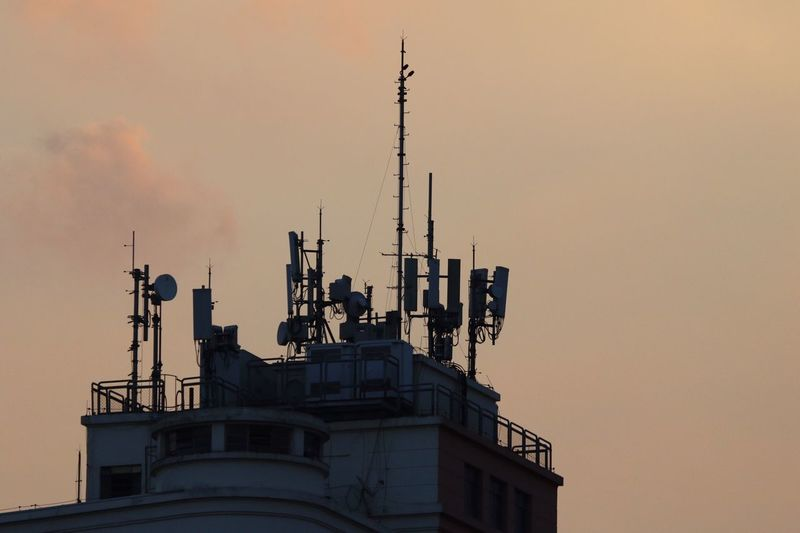 Low angle view of antennas on building against sky during sunset