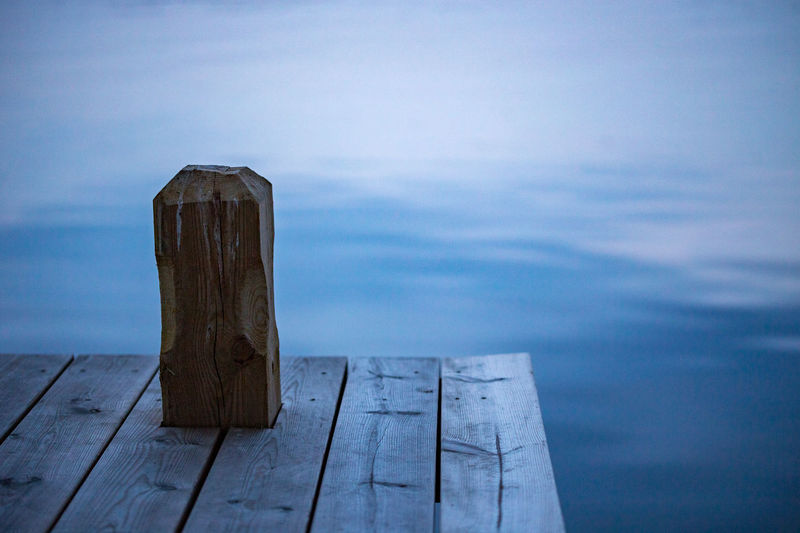 Wooden post on pier by sea against sky