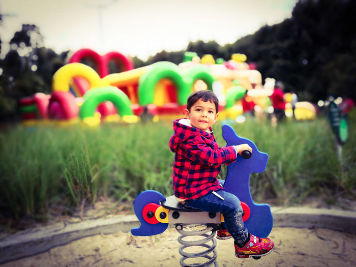 Side view of cute boy sitting on spring ride at playground