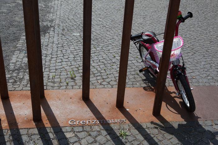 Bike Fence Fences Footpath Memorial Peace Pink TakeoverContrast Tranquility Wall Kids Bike Capture Berlin es ist dieser Widerspruch, der mich in dieser Scene fasziniert... einst stand hier eine Mauer, an der unzählige Menschen umgekommen oder verzweifelt sind und jetzt lehnt ein rosa Kinderfahrrad an eben dieser Stelle. Dieses Kinderfahrrad symbolisiert Reinheit, Freude, Unschuld. Finding New Frontiers The City Light Discover Berlin Focus On The Story