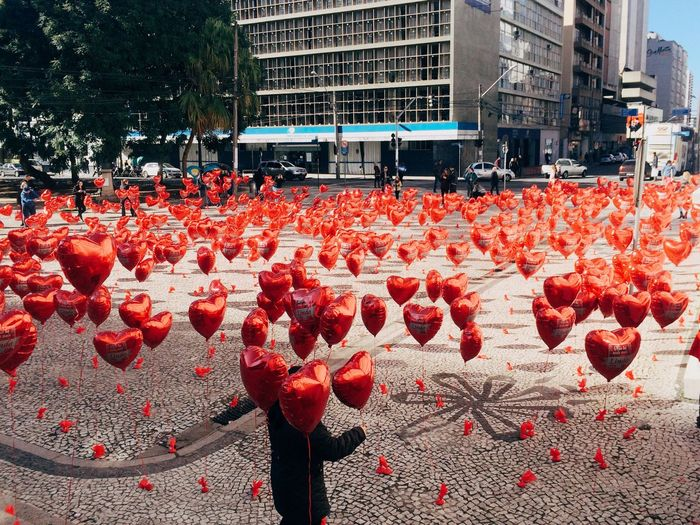 High Angle View Of Person Standing Amidst Red Helium Balloons