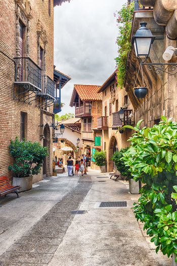 BARCELONA - AUGUST 11: The scenic architecture of Poble Espanyol (in english: spanish village), an open-air architectural museum on Montjuic hill in Barcelona, Catalonia, Spain, on August 11, 2017 Architecture Building Exterior Built Structure Direction Building The Way Forward Nature City Plant Transportation Day Footpath Residential District Road Sky Outdoors Street Incidental People Potted Plant Cloud - Sky