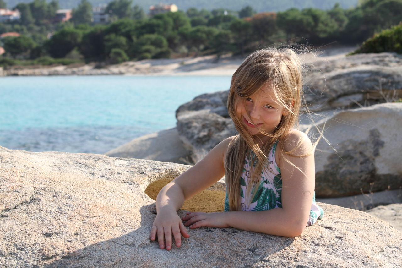 Portrait Of Smiling Girl On Rock In Sunny Day