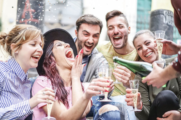 Young happy people making party drinking champagne outdoor Group Of People Men Togetherness Women Youth Young Adult Celebration Fun Drink Champagne Alcohol Party Festive People Happy Celebrate Smiling Happiness Friendship Laughing Celebratory Toast Drinking Glass Event Emotion