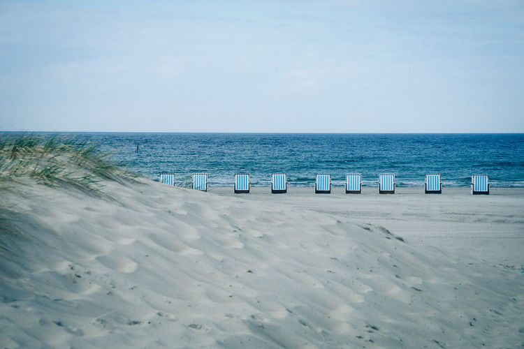 Hooded Beach Chairs On Sea Shore Against Sky