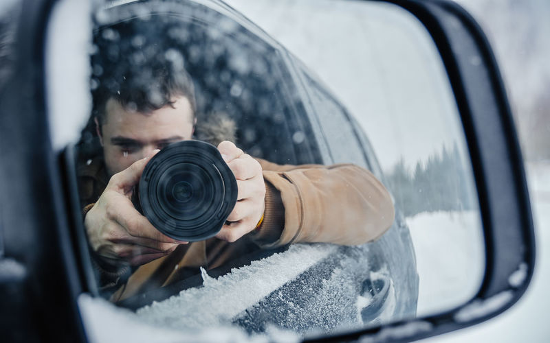 Reflection of man photographing in car