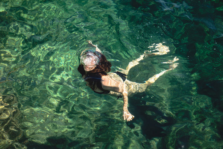 High Angle View Of Young Woman Swimming In Sea