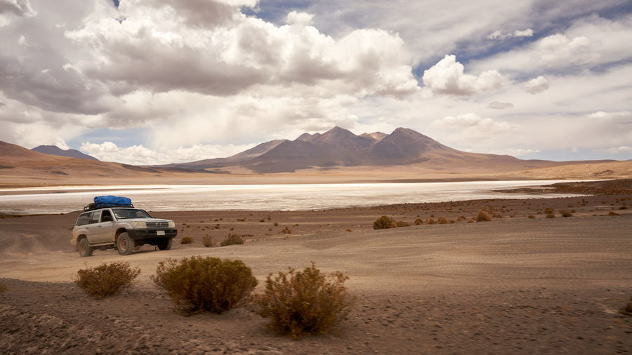 Driving in the Uyuni dessert of Bolivia 4x4 Arid Climate Beauty In Nature Car Cloud - Sky Day Desert Land Vehicle Landscape Mode Of Transport Mountain Mountain Range Nature No People Off-road Vehicle Outdoors Road Salt - Mineral Salt Flat Sand Sand Dune Scenics Sky Transportation