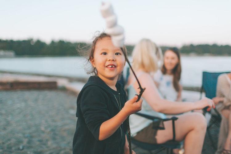 Portrait of happy girl sitting by lake