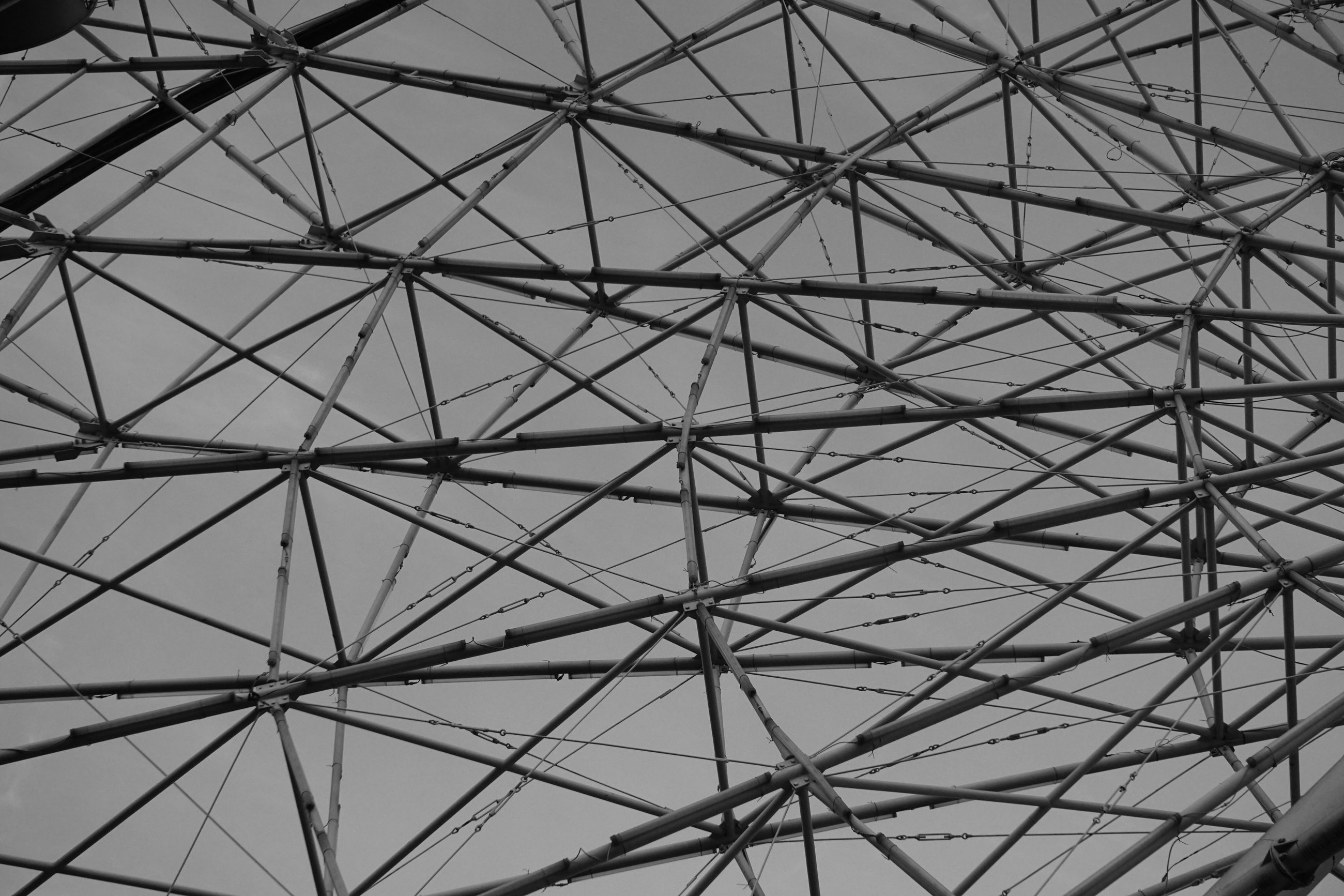 low angle view, built structure, sky, architecture, connection, metal, electricity pylon, day, no people, outdoors, pattern, backgrounds, clear sky, part of, cable, power line, full frame, transportation, modern, nature