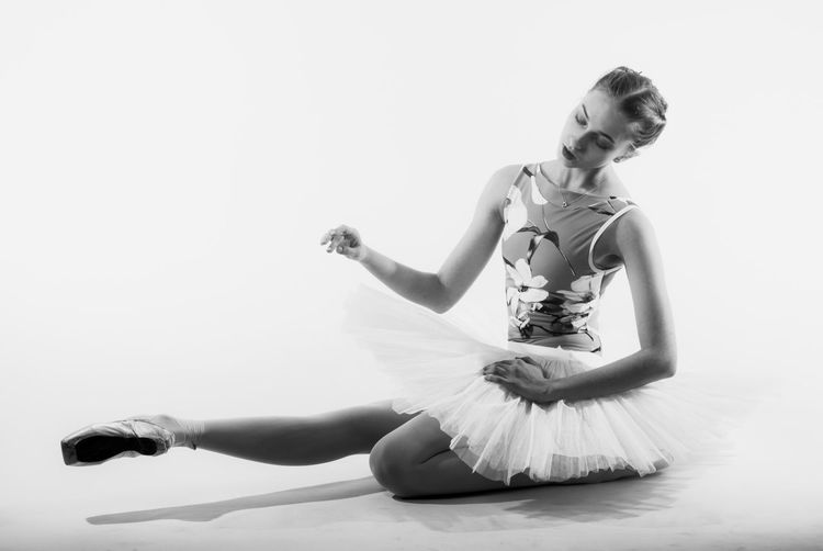 Young woman dancing against white background
