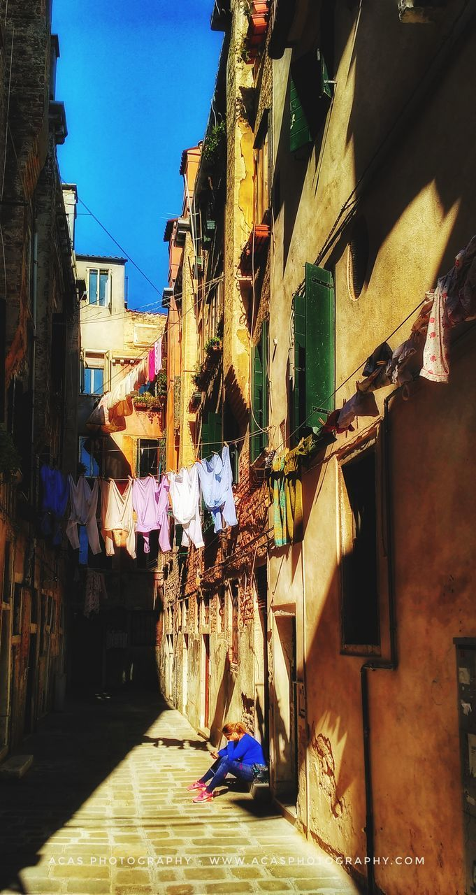 building exterior, architecture, built structure, city, hanging, building, residential district, nature, day, outdoors, laundry, real people, clothing, street, sky, sunlight, people, decoration, clothesline, city life, alley