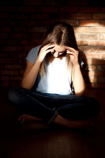 Young woman with headache while sitting at home by brick wall