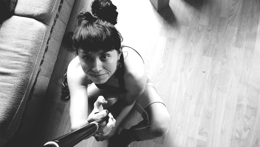 High angle portrait of young woman holding monopod while sitting at home