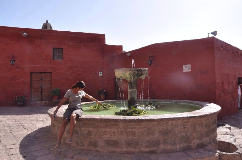 Woman sitting at water fountain