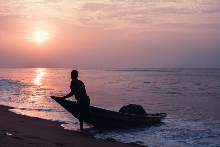A fisherman on beach against sky during sunset