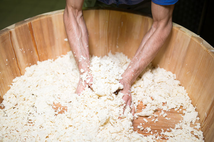 Cropped hands of man crushing cheese in wooden container