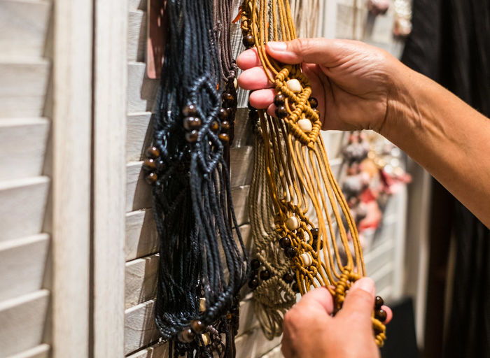 Cropped hand of woman touching decoration hanging on wall