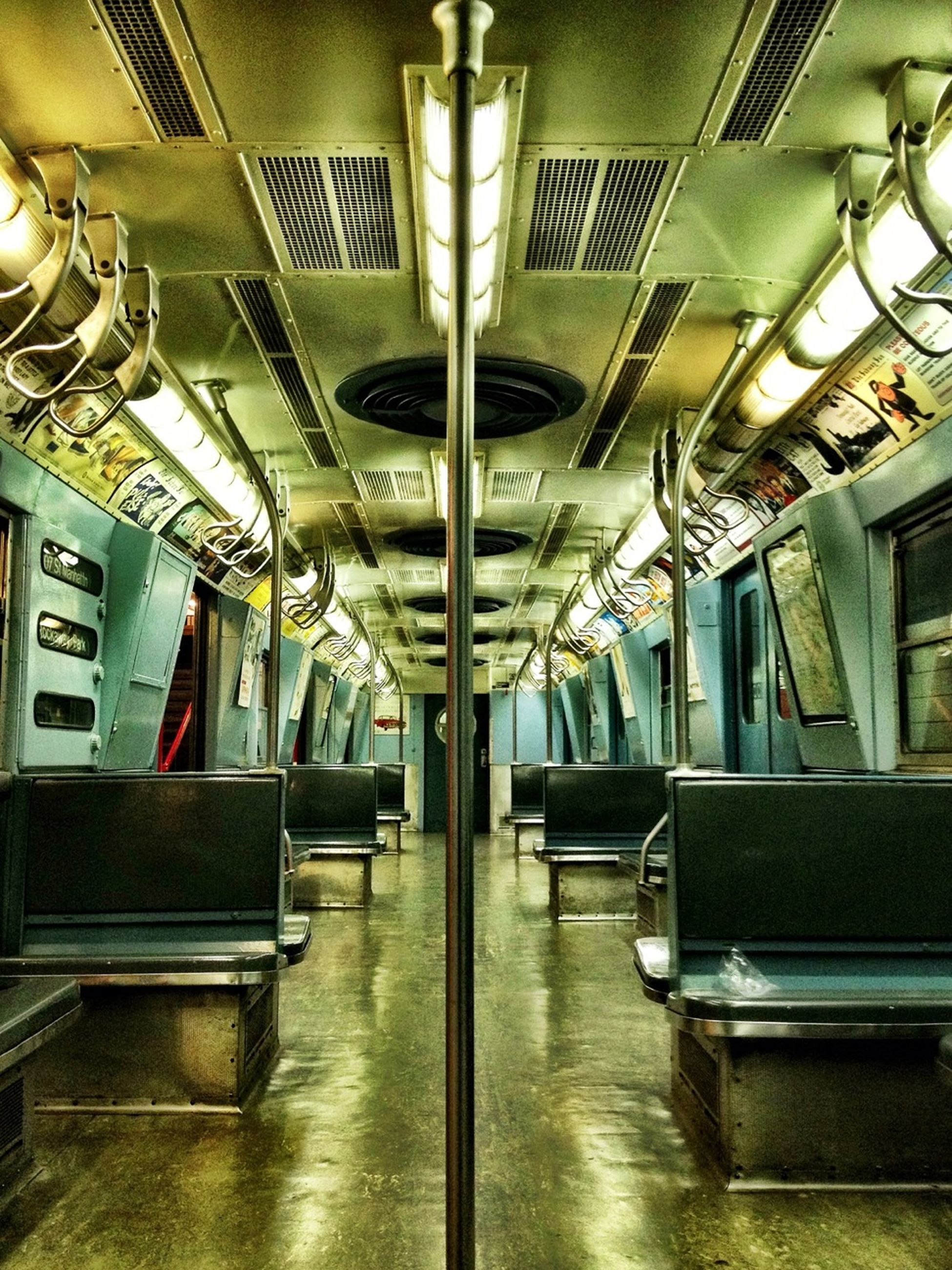indoors, ceiling, illuminated, interior, empty, absence, architecture, lighting equipment, built structure, flooring, modern, window, subway, corridor, reflection, chair, no people, transportation, vehicle seat, in a row