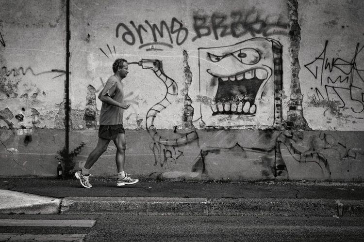 Full length of man skateboarding on street against wall