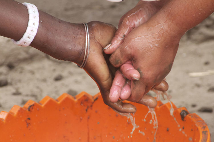 Cropped image of friends washing hands over bucket at beach