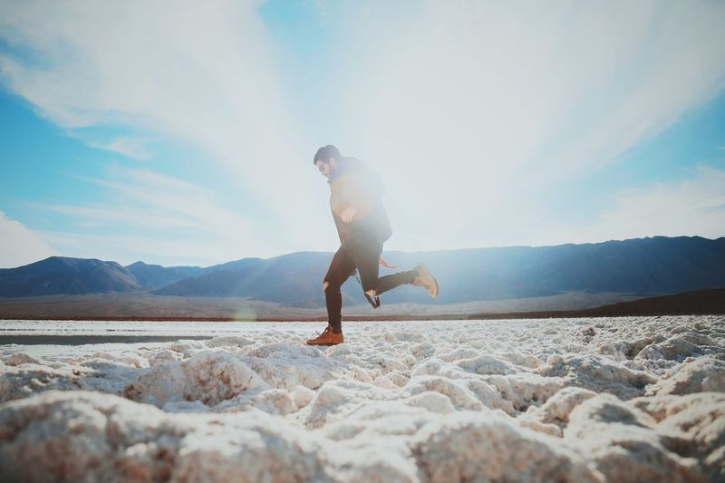 Side view of man jumping on snow during sunny day