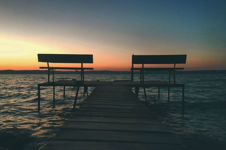 View of empty jetty on pier at sunset