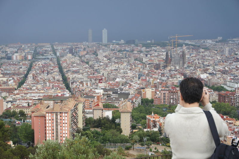 Rear view of man photographing sagrada familia amidst cityscape