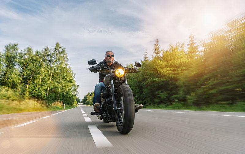 Low Angle View Of Man Riding Motorcycle On Road Against Trees
