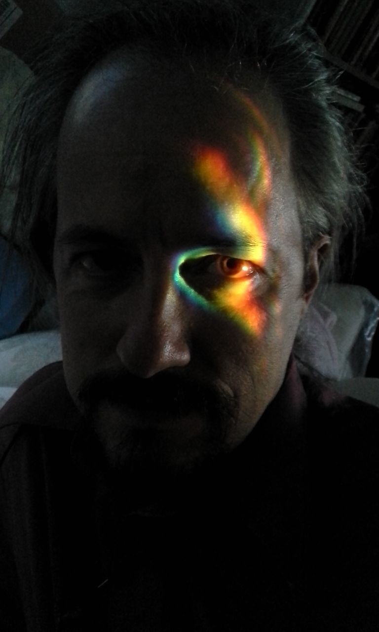 Portrait Of Man With Spectrum Light Falling On Face