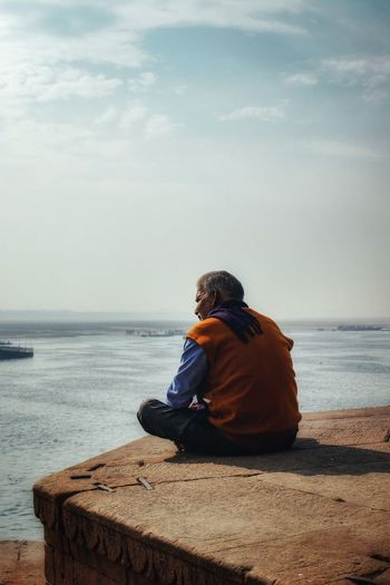 Man sitting on beach looking at sea against sky