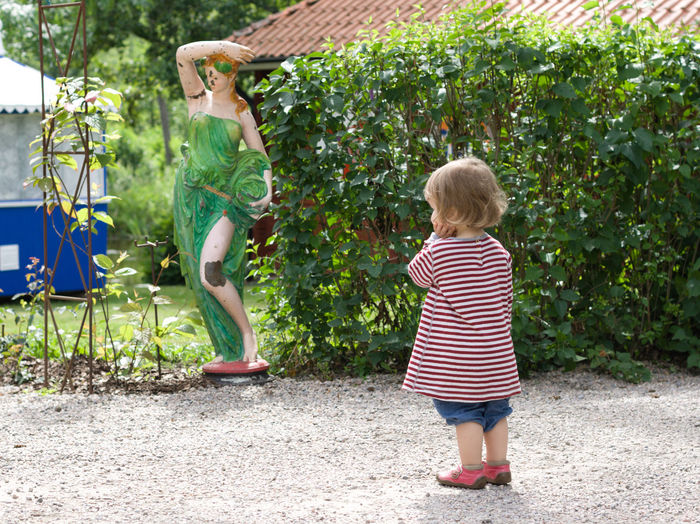 Who is that woman and what is wrong with her knee? Taken at Dufweholms Herrgård in Katrineholm in summer 2016. Childhood Child Full Length Casual Clothing Blond Hair Offspring Standing Statue Outdoors Wondering Innocence Girl Toddler  Scuplture Plastic Hedge Dufweholms Herrgård Decoration Garden Shorts Plant Summer Thinking Marveling Marvelling