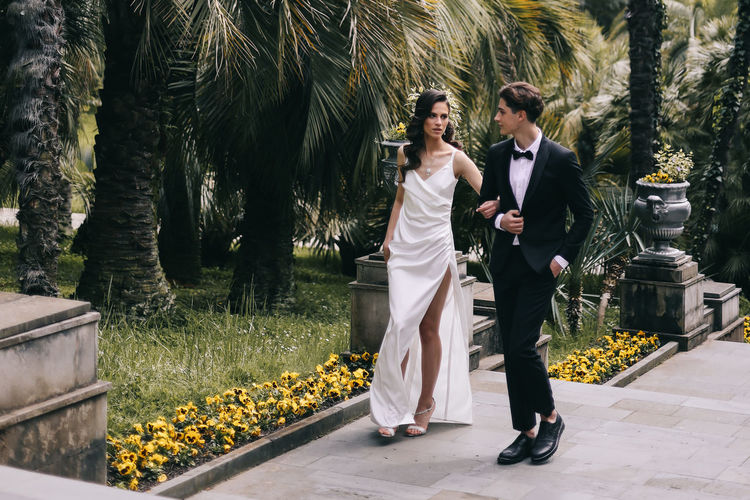 Happy lovers the bride and groom in wedding outfits walk among plants and palm trees in the old park