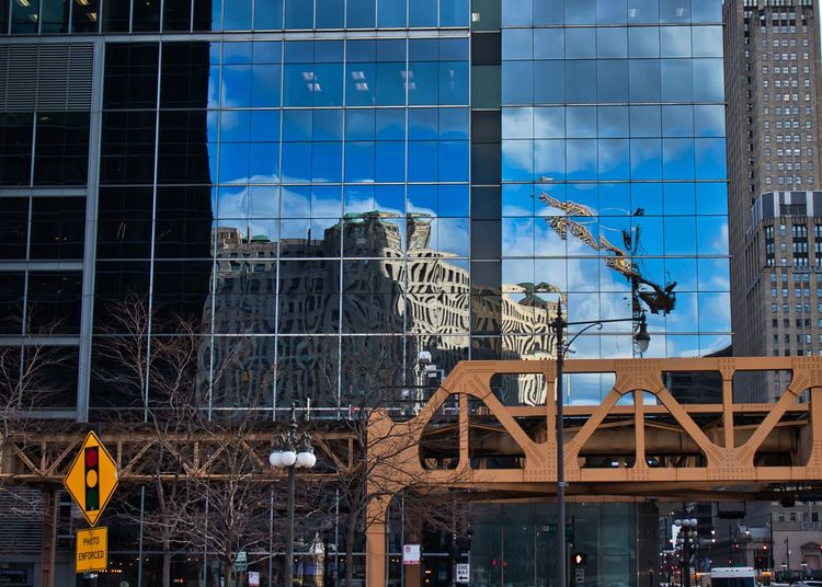Corner of Wacker Drive and Lake Street in Chicago Loop, with Merchandise Mart reflected in a mirrored building exterior, and Photo Enforced streetlight sign near an elevated train track. Waysofseeing Streetlight Photo Enforced Sign Blue Windows Chicago Chicago Loop Construction Crane Wacker Drive Architecture Bridge - Man Made Structure Building Exterior Built Structure City Construction Industry Construction Site Development Glass - Material Lake Street Machinery Merchandise Mart Office Building Exterior Outdoors Photo Enforced Reflection Skyscraper Stoplight Window The Architect - 2018 EyeEm Awards